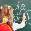 Schoolchild writting on blackboard — Zdjęcie stockowe #12070052
