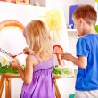 Child painting at easel. — Stock fotografie