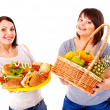 Women choosing between fruit and hamburger. — Stockfoto