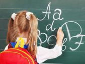 Schoolchild writting on blackboard — Stock Photo