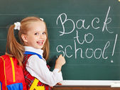 Schoolchild writting on blackboard. — Stock Photo