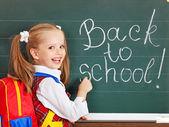 Schoolchild writting on blackboard. — Stock Photo