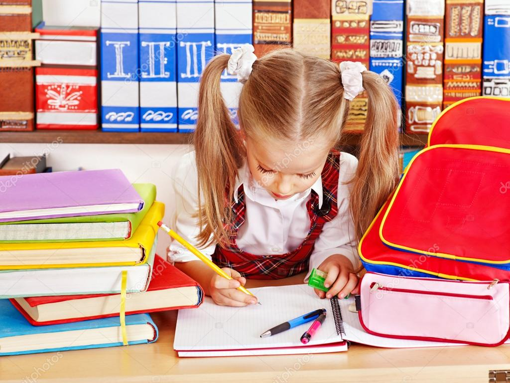 Child with backpack writing in classroom. — Stock Photo #12070050