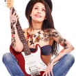Girl with tattoo playing guitar. - Stock Photo