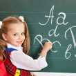 Foto Stock: Schoolchild writting on blackboard
