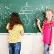Foto Stock: School child writting on blackboard.
