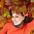 Girl in autumn orange leaves. - Stockfoto