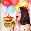 Woman eating hamburger at birthday. - Foto Stock