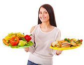 Kvinnan att välja mellan frukt och hamburgare. — Stockfoto