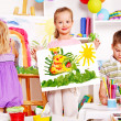 Child painting at easel. - Foto Stock