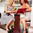 Women at laptop drinking cocktail in a cafe. - Foto Stock
