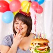 Woman eating hamburger at birthday. — Stock Photo #12802456