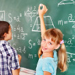 School child writting on blackboard. - Foto Stock