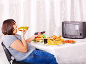 ファーストフードを食べ、テレビを見ている女性. — ストック写真