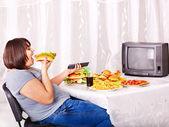 Hızlı yemek yeme ve tv izlerken kadın. — Stok fotoğraf