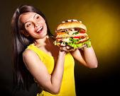 Woman holding hamburger. — Stock Photo