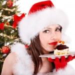 meisje in Kerstman hoed eten taart door kerstboom — Foto de Stock   #12810867