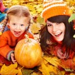 Happy family with pumpkin on autumn leaves. — Stock Photo #12817988