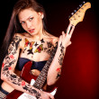Girl with tattoo playing guitar. - Photo