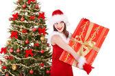 Menina segurando a caixa de presente pela árvore de natal. — Foto Stock