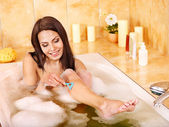 Woman shaving her legs in bath. — Stock Photo