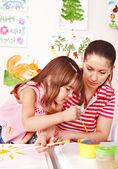 Little girl painting with teacher in preschool. — Stock Photo