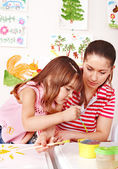 Little girl painting with teacher in preschool. — Stock Photo