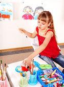 Dítě s obrázkem a štětec v herně. — Stock fotografie