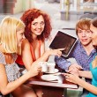 Group with tablet computer at cafe — Stock Photo