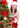 Young woman in Santa hat near Christmas tree. Isolated. - Stock Photo