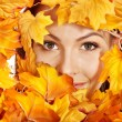 Stock Photo: Woman holding orange leaves.