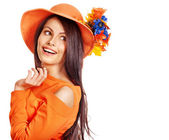 Happy woman wearing orange hat with flower. — Stock Photo