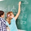School child writting on blackboard. — Stock Photo