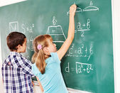 School child writting on blackboard. — Foto Stock