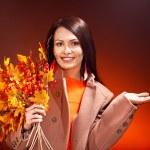 Woman holding orange leaves. — Stock Photo #13464317