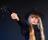 Witch girl with magic wand casting spells. — Stock Photo