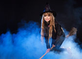 Girl in witch's hat flying on broomstick. — Stock Photo