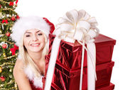 Christmas girl in santa hat holding stack gift box. — Stock Photo