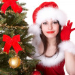 Photo: Christmas girl in santa hat with hand near ear listen and fir tree.