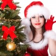 Christmas girl in santa hat with hand near ear listen and fir tree. — Stockfoto