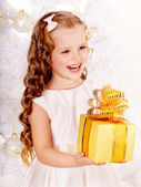 Child with gift box near white Christmas tree. — Stock Photo