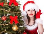 在用耳朵听着和杉木树附近的手圣诞老人帽子圣诞女孩. — 图库照片
