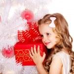 Child with gift box near white Christmas tree. — Stock Photo #13783733