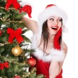Girl in Santa hat near  Christmas tree. - Foto Stock
