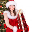 Girl in Santa hat with gift box near Christmas tree. - Foto Stock