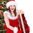 Girl in Santa hat with gift box near Christmas tree. — Stock fotografie