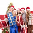 Stock Photo: Group in santa hat holding stack gift box.