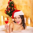 Woman in santa hat relax in bath. - Stock Photo
