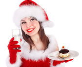 Girl in red Santa hat eating cake on plate. — Stock Photo