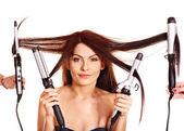 žena drží vlasy curlingu železa. — Stock fotografie